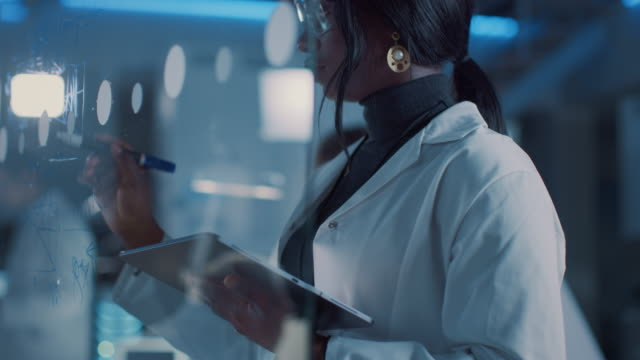 in the research laboratory smart and beautiful african american female scientist wearing white coat and protective glasses writes formula on glass whiteboard, references her tablet computer - inżynieria filmów i materiałów b-roll