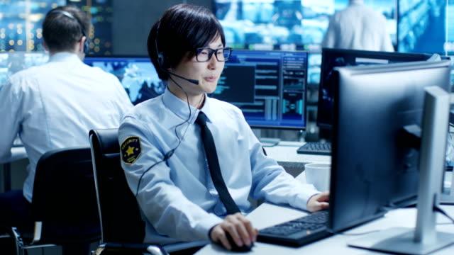 セキュリティ コマンド センターに彼のワークステーションのモニターの責任者は画面し、パトロール ヘッドセットを介して通信します。彼は、監視チームの一部です。 - オペレーター 日本人点の映像素材/bロール
