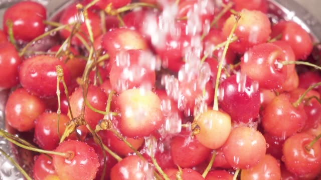 In the sink cherry in a colander under the water slow motion video