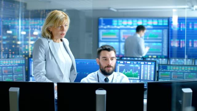 an der börse firma chief executive gespräche mit professionellen trader. sie sind umgeben von bildschirmen mit grafiken und ticker zahlen. - unterordnung stock-videos und b-roll-filmmaterial