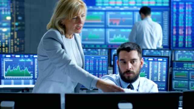 An der Börse Firma Chief Executive Gespräche mit professionellen Trader. Sie sind umgeben von Bildschirmen mit Grafiken und Ticker zahlen. – Video