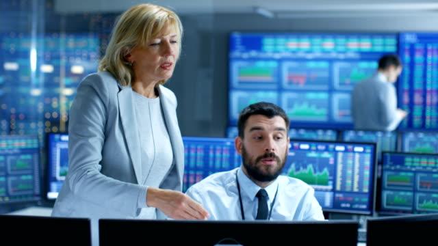 an der börse spricht festen leiter der abteilung mit professionellen trader. sie sind umgeben von bildschirmen mit grafiken und ticker zahlen. - unterordnung stock-videos und b-roll-filmmaterial