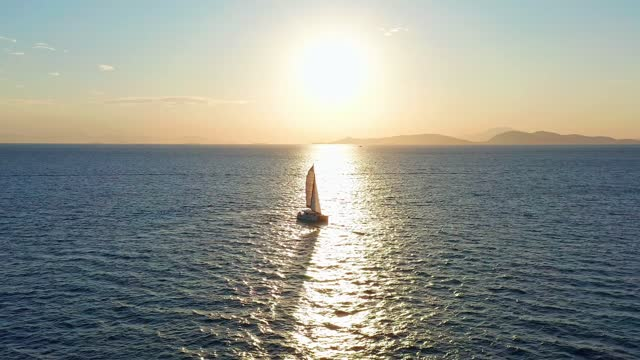In the sunshine, a sailing boat sails slowly on the sea.