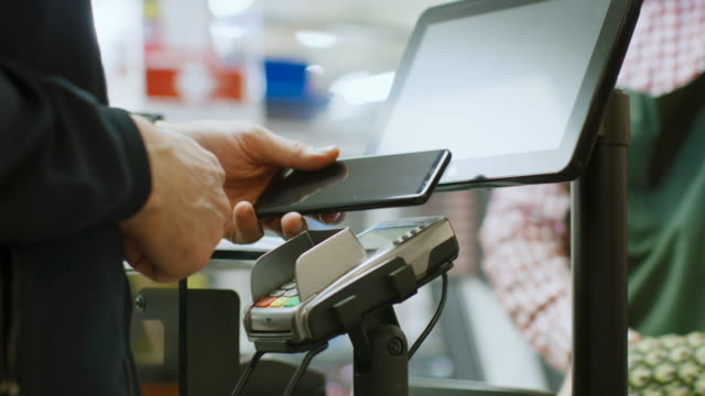 vídeos de stock e filmes b-roll de in the supermarket close-up footage of the man paying with smartphone at the checkout counter. using modern and convenient wireless nfc paying system in big mall. - tote bag