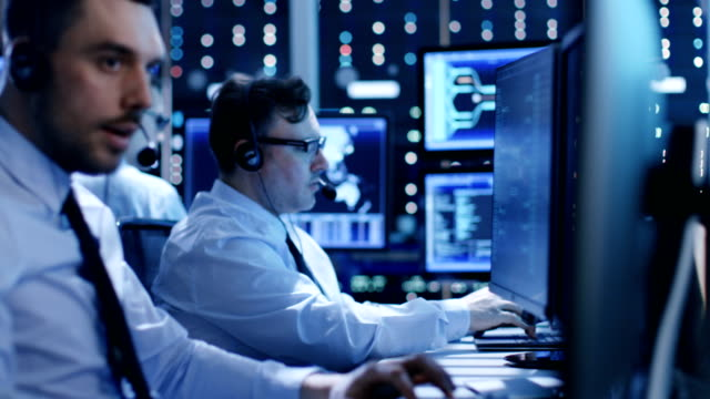 In the System Control Center Technical Support Team Gives Instructions with the Help of the Headsets. Possible Air Traffic/ Power Plant/ Security Room Theme. video