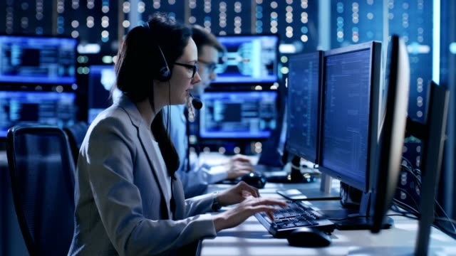 in the system control center technical support team gives instructions with the help of the headsets. possible air traffic/ power plant/ security room theme. - call center stock videos and b-roll footage