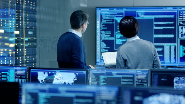 in the system control room it specialist and project engineer have discussion, they're surrounded by multiple monitors with graphics. they work in a data center on data mining, ai and neural networking. - безопасность сети стоковые видео и кадры b-roll