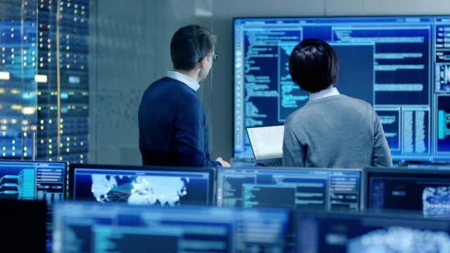 stockvideo's en b-roll-footage met in het systeem controle kamer het specialist en project engineer hebben discussie, zijn ze omringd door meerdere beeldschermen met afbeeldingen. ze werken in een data center op datamining, ai en neurale netwerken. - datacenter