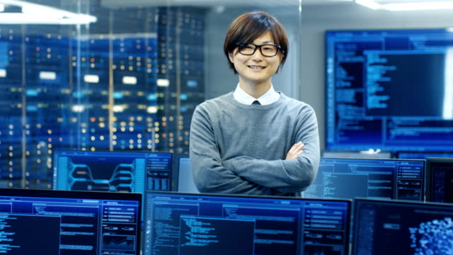In the System Control Room IT Technician Crosses Arms and Smiles. He's Surrounded by Multiple Displays Showing Graphics. video