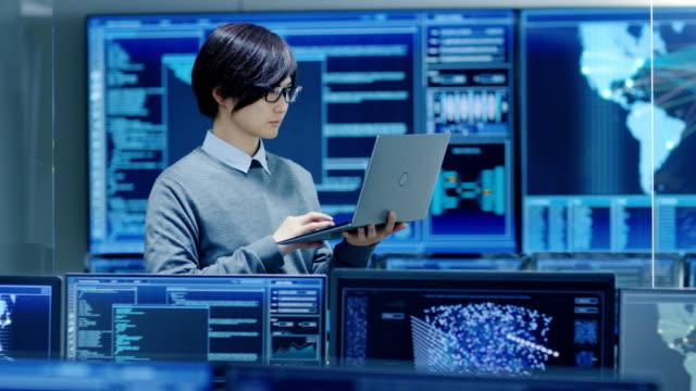 i systemkontroll rum det tekniker håller och fungerar på en laptop, i bakgrunden flera bildskärmar med grafik. anläggningen fungerar på artificiell intelligens, stora datamining, neurala nätverk, surveillance project. - server room bildbanksvideor och videomaterial från bakom kulisserna