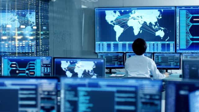 i systemet kontroll rummet operatör sitter på sin arbetsplats med flera bildskärmar visar grafik och logistikinformation. - server room bildbanksvideor och videomaterial från bakom kulisserna