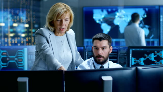 In the System Control Room Senior Technical Supervisor Observes Work of the Operator. In the Background People Working and Monitors Showing Relevant Technical Data. In the System Control Room Senior Technical Supervisor Observes Work of the Operator. In the Background People Working and Monitors Showing Relevant Technical Data. cybersecurity stock videos & royalty-free footage