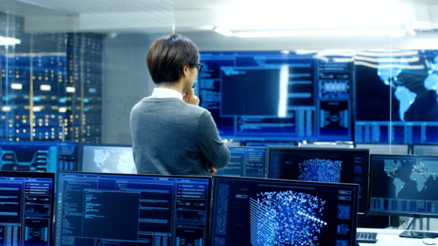 In the System Control Room Technical Operator Stands and Monitors Various Activities Showing on Multiple Displays with Graphics. Administrator Monitors Work of  Artificial Intelligence, Big Data Mining, Neural Network, Surveillance Project. video