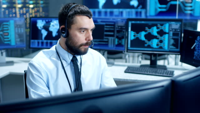 in the system monitoring room dispatcher speaks into headset, observers proper functioning of the facility. he's surrounded by screen showing technical data. - call center стоковые видео и кадры b-roll