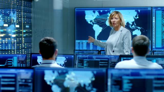 システム監視室の主任女性彼女の下位の専門家のための説明会を開催、その目標とタスクについて説明します。彼らはハイテク環境で動作します。 - コントロール点の映像素材/bロール