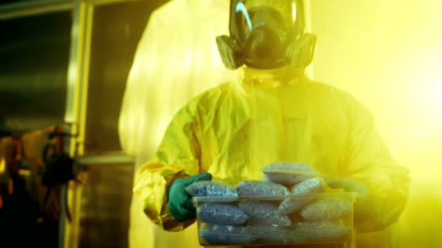 In the Underground Drug Laboratory Clandestine Chemist Walks with a Box of Newly Cooked and Packed Batch of Blue Crystal Methamphetamine. He Has Organized Fully Equipped Laboratory in the Abandoned Building. video