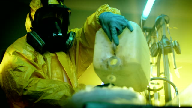 In the Underground Drug Laboratory Clandestine Chemist Wearing Protective Mask and Coverall Mixes Chemicals. He Pours Liquid From Canister into Bowl, Toxic Compounds Create Smoke. He Works in the Abandoned Building. video