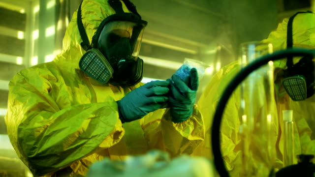 In the Underground Drug Laboratory Clandestine Chemist Wearing Protective Mask and Coverall Holds Bag with Blue Meth Amphetamine. His Team Synthesises Illegal Substances in the Abandoned Building. video