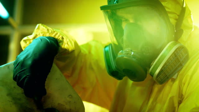 In the Underground Drug Laboratory Clandestine Chemist Wearing Protective Mask and Coverall Mixes Chemicals. He Pours Liquid From Canister into Bowl to Make New Batch of Synthetic Narcotics. He Squats in the Abandoned Building. video