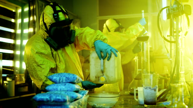 In the Underground Drug Laboratory Clandestine Chemists Wearing Protective Masks and Coveralls Mix Chemicals. One Pours Liquid From Canister into Bowl, Second Checks Beaker for Product Consistency. They Work in the Abandoned Building. video
