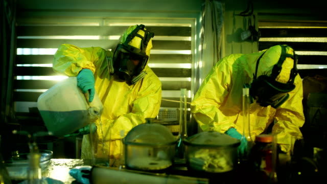 In the Underground Drug Laboratory Clandestine Chemists Wearing Protective Masks and Coveralls Mix Chemicals for Synthesising New Batch of Addictive Narcotics. They Work in the Abandoned Building. video