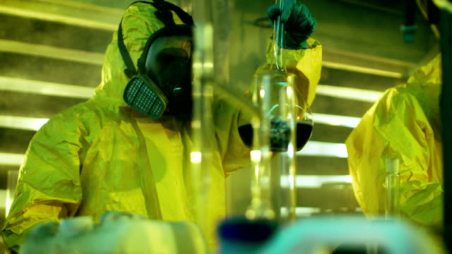 In the Underground Drug Laboratory Team of Clandestine Chemists Synthesises Illegal Drugs, One Holds Beaker with Chemicals and Checks it's Consistency. They Cook Drugs in the Abandoned Building. video