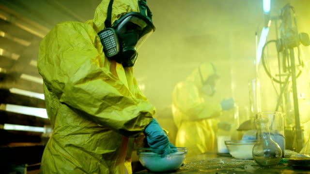 In the Underground Drug Laboratory Two Clandestine Chemists Cook Synthetic Drugs, Crush Them in a Bowl and Package for Further Distribution. They Wear Protective Gas Masks and Coveralls and Squat in the Abandoned Building. video