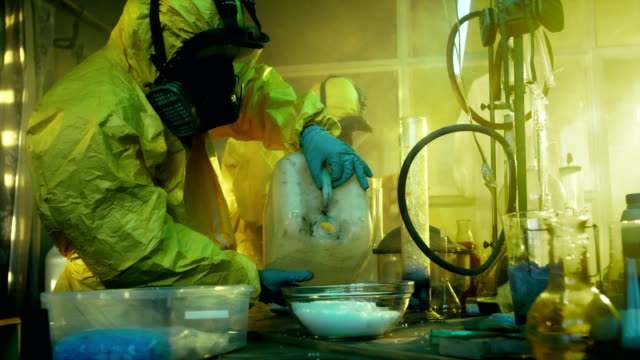 In the Underground Drug Laboratory Two Clandestine Chemists Covered in Protective Coveralls and Gas Masks Mix Chemicals to Synthesise Drugs. They Work in the Abandoned Building. video