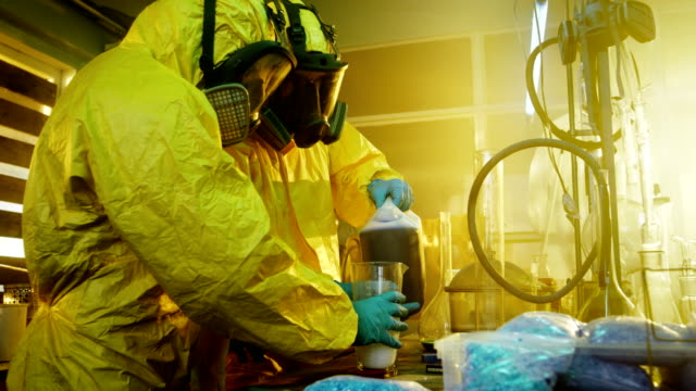In the Underground Drug Laboratory Two Clandestine Chemists Mix Chemicals while Cooking Narcotics. They Use Canisters and Beakers, Toxic Compounds Create Smoke. They Work in the Abandoned Building. video