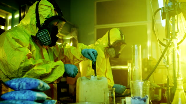 In the Underground Drug Laboratory Two Clandestine Chemists Wearing Protective Masks and Coveralls Use Hosepipe For Drug Distillation. They Cook Synthesised Drugs in the Abandoned Building. video