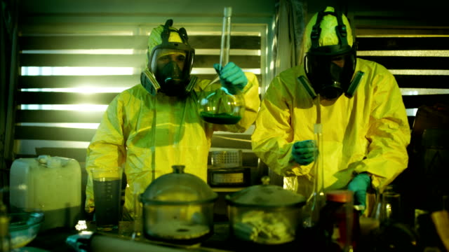 In the Underground Drug Laboratory Two Clandestine Chemists Wearing Protective Masks and Coveralls Test Cooked Drug's Purity and Strength. They Work in the Abandoned Building Full of Glassware and Cooking Equipment. video
