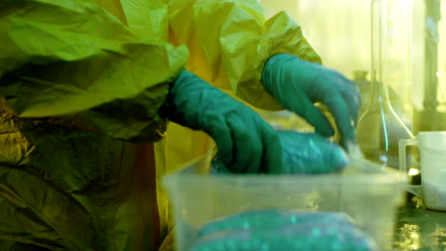 In the Underground Laboratory Clandestine Chemists in Protective Coveralls Package For Distribution Newly Cooked Batch of Drugs. They Illicitly Cook Drugs with Special Lab Equipment in the Abandoned Laboratory. video