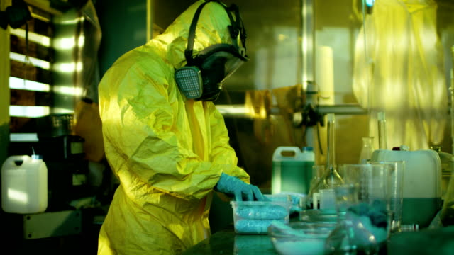 In the Underground Laboratory Clandestine Chemists in Protective Coveralls Pack Newly Cooked Batch of Drugs in the Bags for Further Street Distribution. They Illicitly Cook Drugs with Special Lab Equipment in the Abandoned Laboratory. video