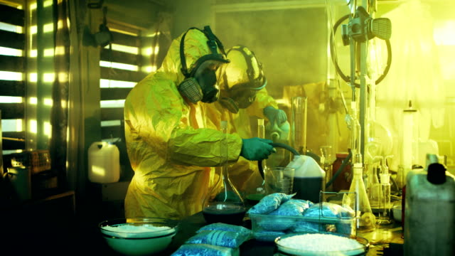 In the Underground Laboratory Two Clandestine Chemists Cook Drugs. They Wear Masks and Coveralls and Work with Beakers and Toxic Chemical Compounds. video