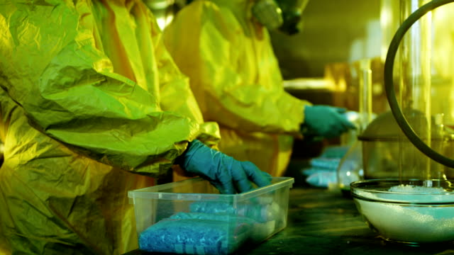 In the Underground Laboratory Two Clandestine Chemists Pack Bags of Drugs into Boxes. Laboratory is Full of Illegal Equipment. They Squat in an Abandoned Building. video