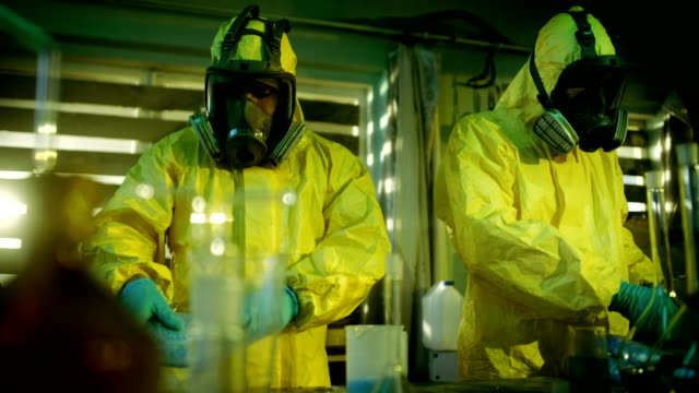 In the Underground Laboratory Two Clandestine Chemists Pack Bags of Drugs into Boxes. Laboratory is Full of Glassware and Other Narcotics Production Related Equipment. They Squat in an Abandoned Building. video
