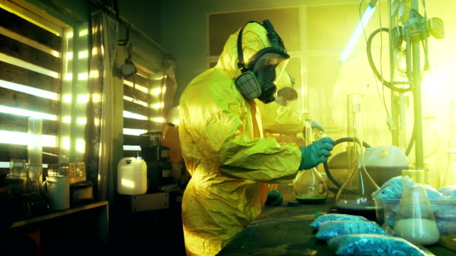 In the Underground Laboratory Two Clandestine Chemists Wearing Protective Coveralls and Masks Cook Drugs. They Work with Beakers, Distillation Glassware, Canisters and Hosepipe. True Crime Concept. video