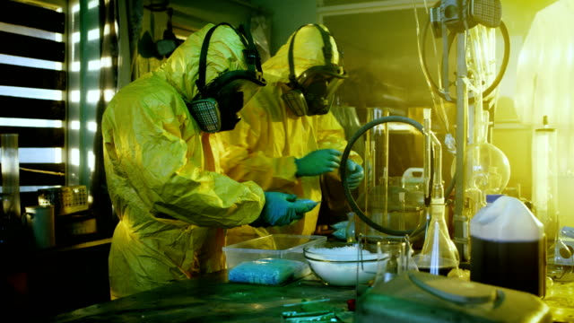 In the Underground Laboratory Two Clandestine Chemists Wearing Protective Masks and Coveralls Pack Bags of Synthesised Crystal Meth into Boxes for Further Distribution. Laboratory is Full of Illegal Equipment. They Squat in an Abandoned Building. video