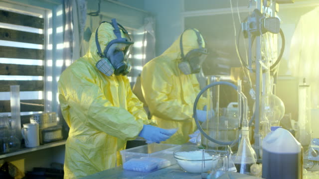 In the Underground Laboratory Two Clandestine Chemists Wearing Protective Masks and Coveralls Pack Bags Full of Crystal Meth into Boxes. Laboratory is Full of Illegal Equipment. They Squat in an Abandoned Building. video