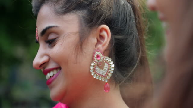 In Traditional Dress A Pakistani female in a red sari is smiling away from the camera she is wearing ear rings and has a Bindi on her forehead. indian culture stock videos & royalty-free footage