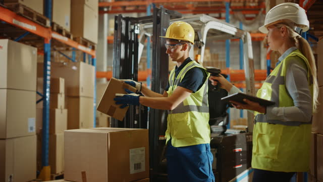 In Warehouse Manager Uses Digital Tablet and Scans Cardboard Boxes for Inventory, Talks with Forklift Driver about Package Delivery. Workers in Global Distribution Center with Shelves with Goods