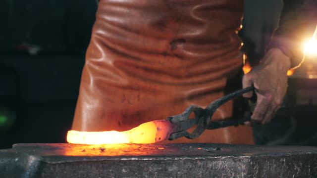 Incandescent metal element is getting forged. Slow motion. Incandescent metal element is getting forged. HD anvil stock videos & royalty-free footage