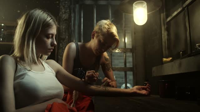 incarcerated tattoo master tattooing blonde women at prison - tatuaż filmów i materiałów b-roll