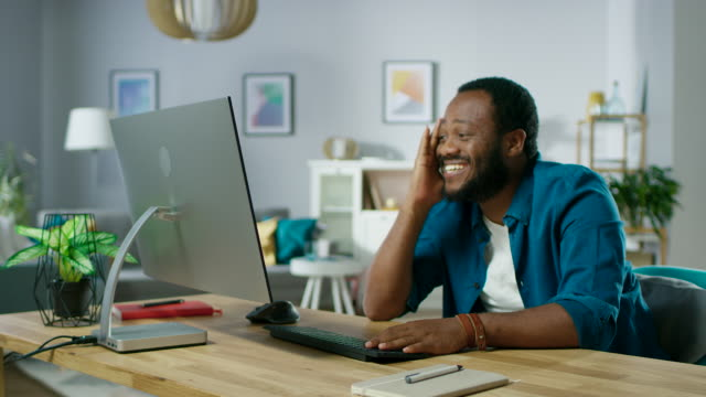 Includes Audio: Handsome Man Has Fun while Using Personal Computer at Home, Watching Funny Videos or Internet Content He Laughs out Loud Looking at the Camera.