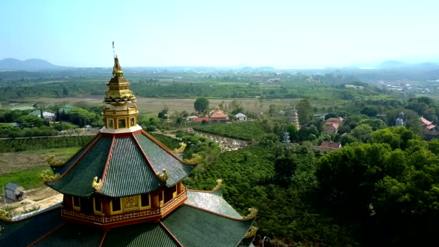 incredible rural valley with temple roof on foreground flycam shows incredible rural tropical valley with scenic Buddhist temple green roofs on foreground sri lankan culture stock videos & royalty-free footage