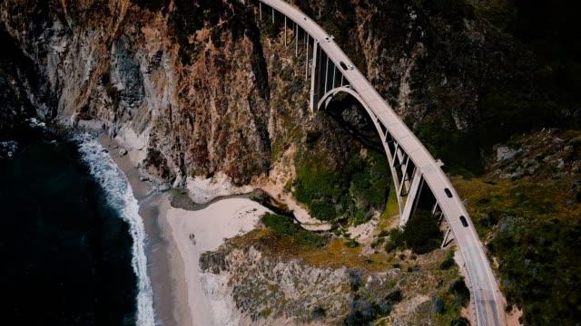 vídeos de stock e filmes b-roll de incredible top view aerial shot of highway 1 at bixby creek bridge with amazing mountains and ocean big sur california. - big sur