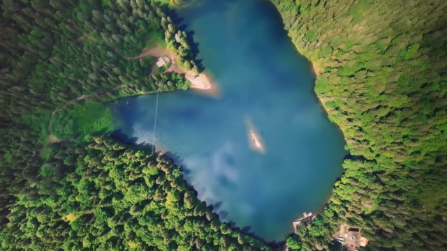 Incredibly beautiful blue lake surrounded by green pines and firs in the mountains View from above video