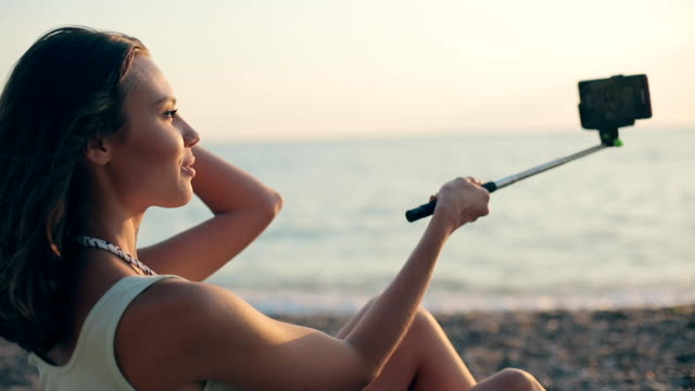Incredibly beautiful model making selfie on the phone using a monopod sitting near the sea at sunset Incredibly beautiful model making selfie on the phone using monopod sitting near the sea at sunset charming stock videos & royalty-free footage