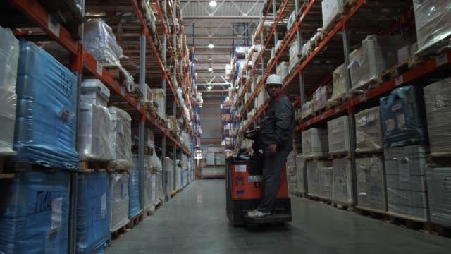 incredibly large logistic warehouse. a man on a car passes by the camera. 4k slow mo - rozładowywać filmów i materiałów b-roll