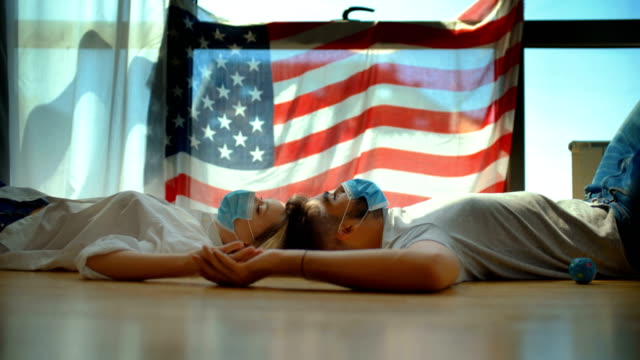 Independence day under lockdown. Closeup side view of a young couple spending Independence day indoors with face masks on. American flag is spread on the window, they are on the floor and talking. fourth of july videos stock videos & royalty-free footage